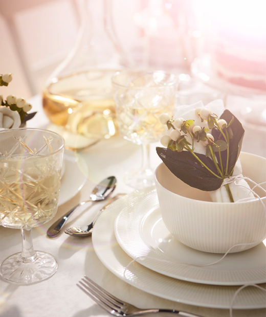 Image of individual place setting in all white, with glasses, tableware and floral decorations creating a feeling of luxury.