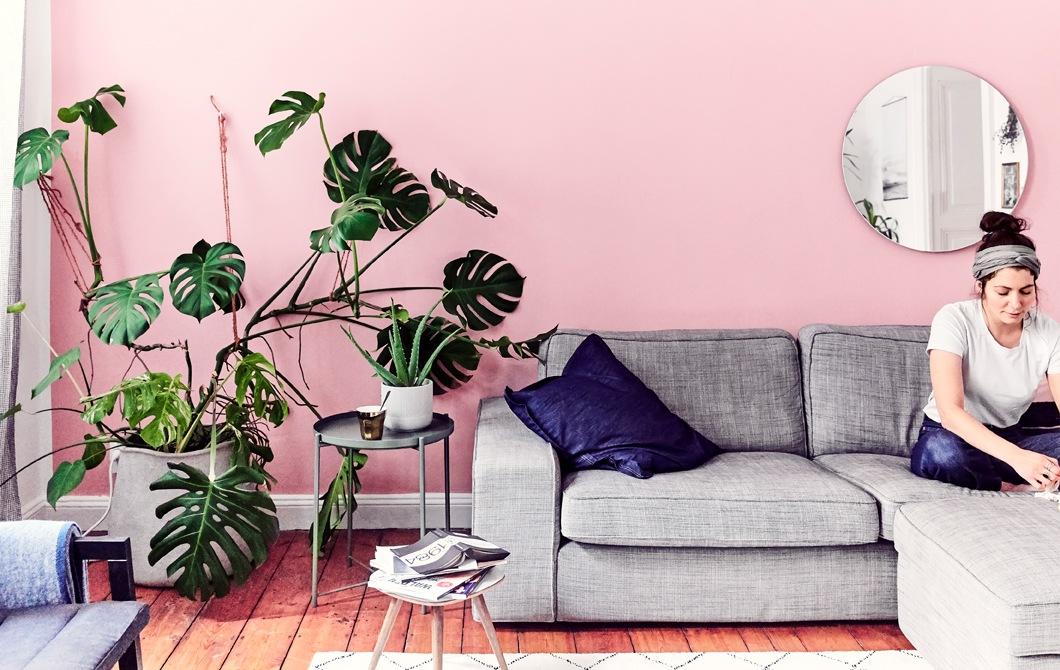 Julia坐在客廳的灰色梳化上,背後是粉紅色牆,旁邊有一大盆龜背竹。