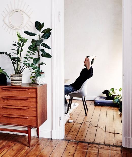 透過房門看到坐在椅子上的André,房內鋪上木地板,還有一些復古傢具。