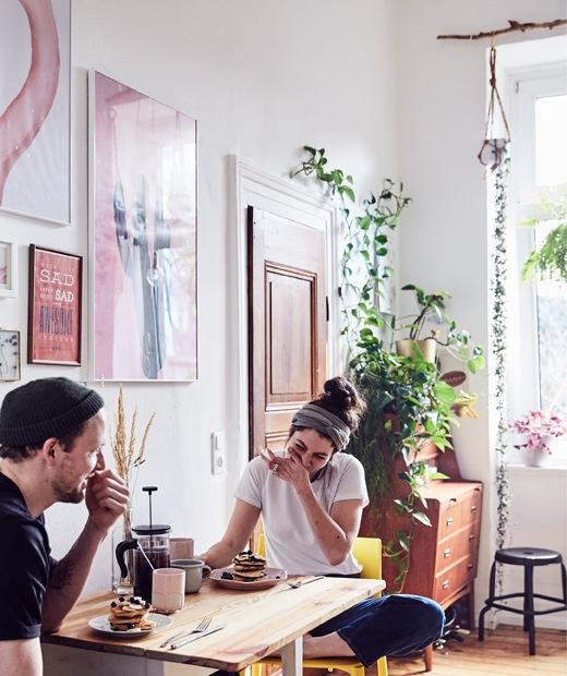 Julia及André在摺板檯吃早餐,房內有植物,牆上有藝術品。