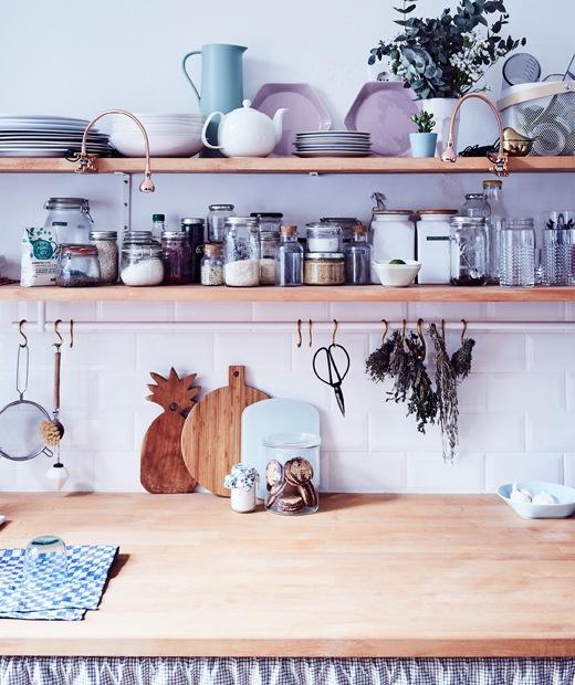 放在兩個木層架上的玻璃瓶及餐具,下面是廚房木製櫃台板。