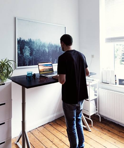 André在白色房間的升降式書檯旁工作,牆上有一幅大森林照片。