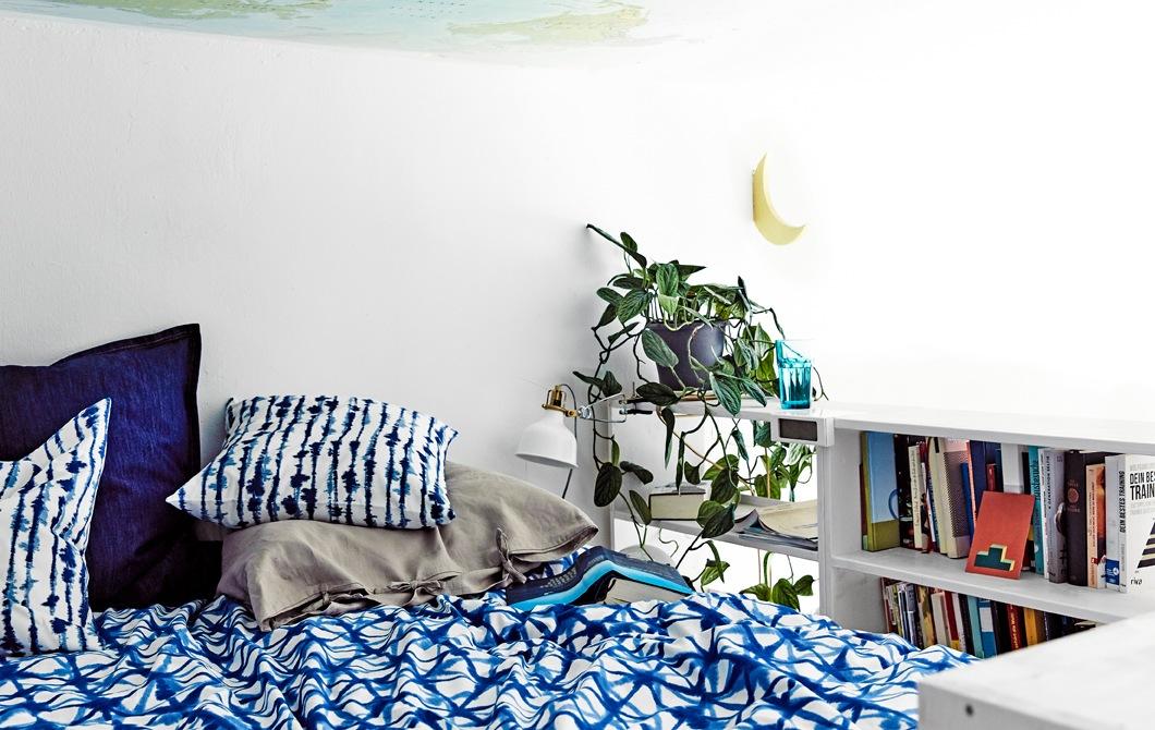 鋪上藍色印花床上用品的睡床,旁邊有一個書架。