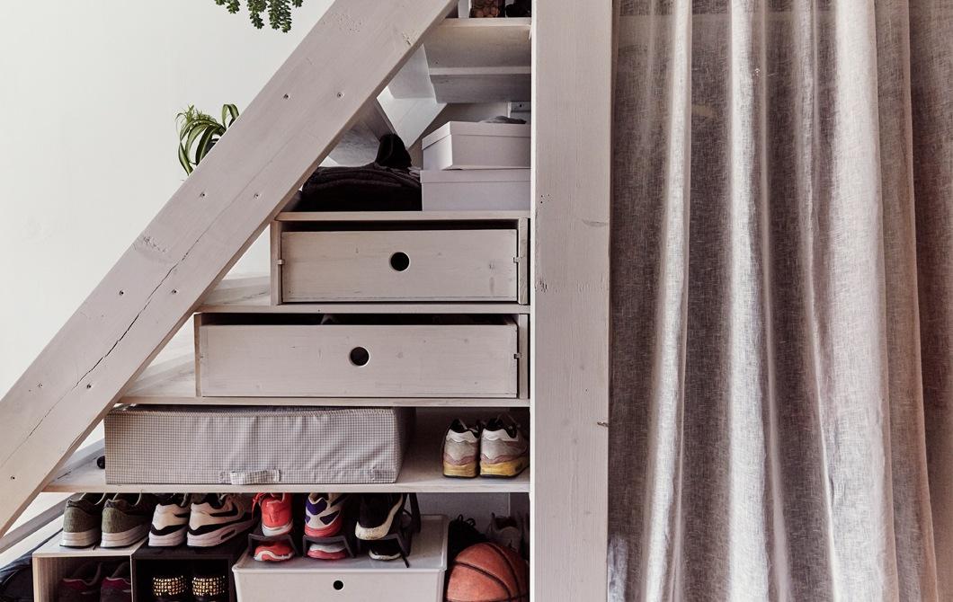 放在樓梯底層架上的貯物箱及鞋。