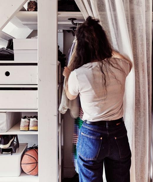 Julia伸手到樓梯底的衣櫃拿取布簾後的衣服。