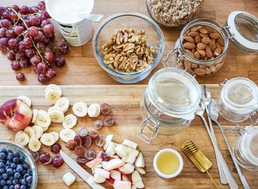 炮製早餐需要切粒生果、果仁及玻璃瓶,全部放在木砧板上。