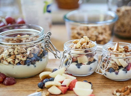 裝著乳酪、穀麥、鮮果及果仁的三個玻璃瓶,全部放在木砧板上。
