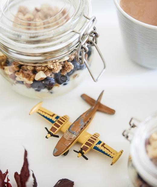 盛載穀麥的玻璃瓶及飛機玩具,全部放在白色枱面上。