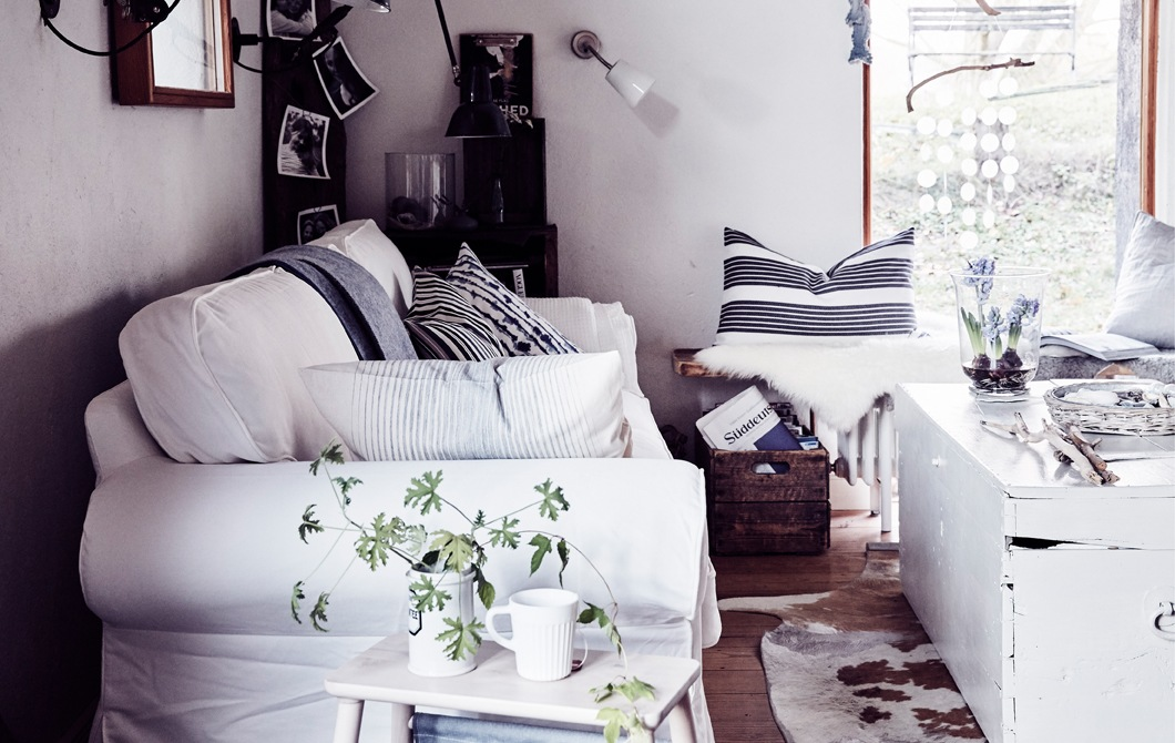 A white traditional-style sofa in a living room with striped cushions, vintage wooden trunk and natural materials.