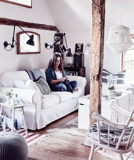 Claudia sitting on a white sofa in a living room with wooden beams and floorboards.