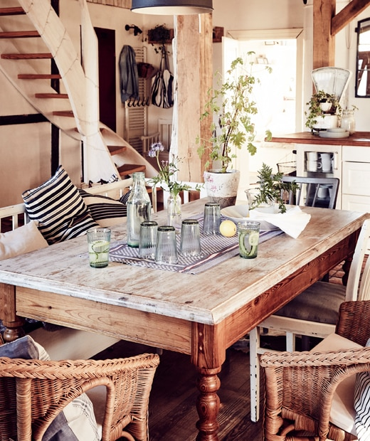 A vintage wooden dining table with rattan armchairs in an open living space.
