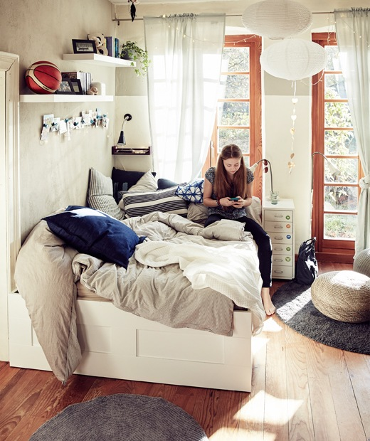 Malin sitting on a double bed with throws and cushions in a bedroom with large windows.