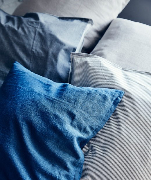 Cushions in shades of blue on a grey sofa.
