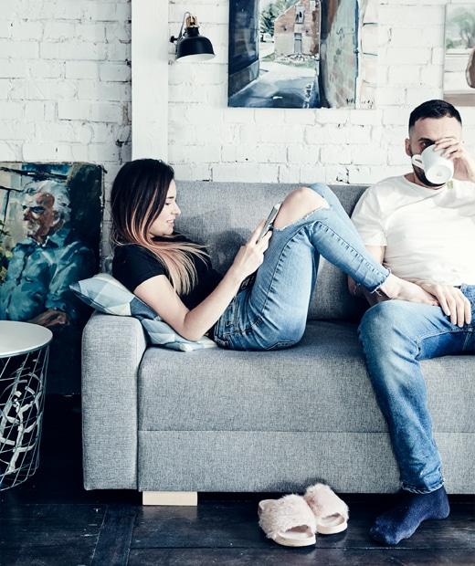 Katarzyna and Mikolaj relaxing on their grey sofa.