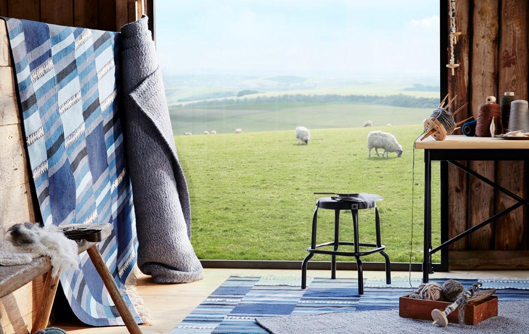 在木屋內有攤開或捲起的藍色和灰色地氈,屋外的草地有幾隻綿羊。