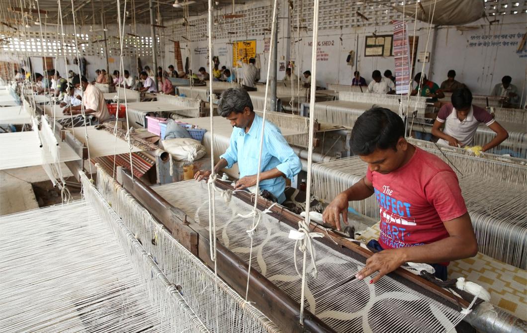 工人在大型工場用織布機編織羊毛。