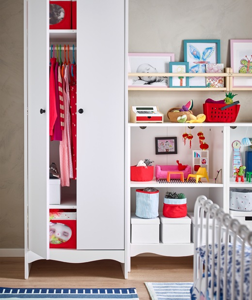 Red clothes and boxes in a tall white wardrobe, and books, toys and boxes on open shelves.
