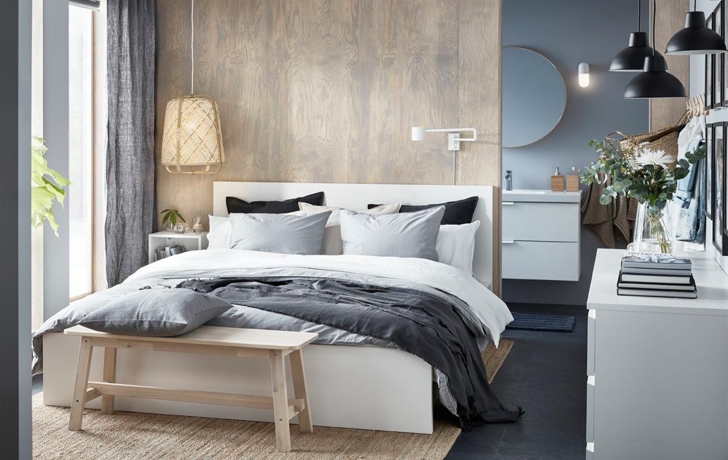 中性色調的睡房放有雙人床、木長几和柳枝編織燈。