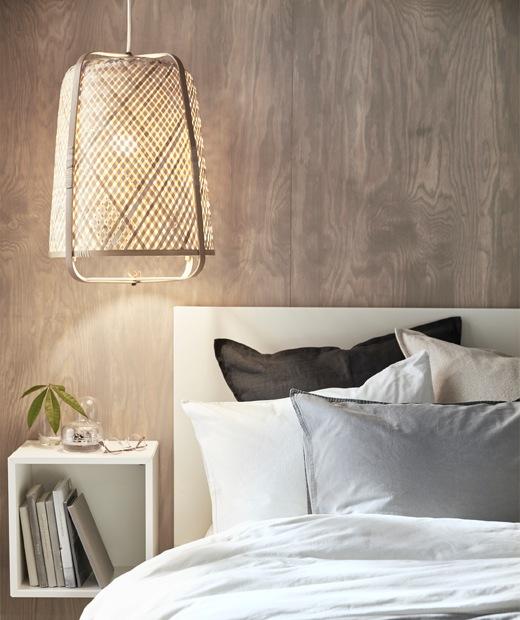 一盞竹燈掛在睡床上方,背後的木板牆有方形貯物組合。