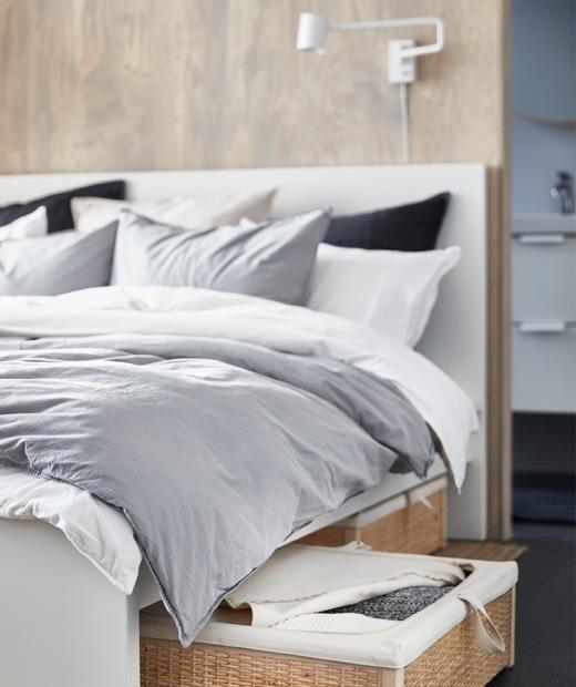 採用灰色和白色寢具的睡床,床下放有織藤貯物箱。