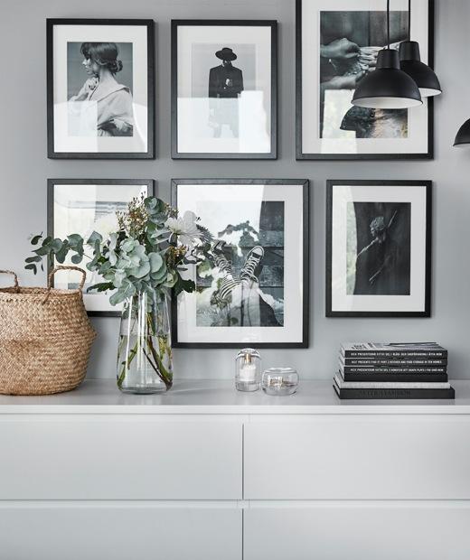 兩個白色抽屜櫃上方有一幅黑白色照片牆。