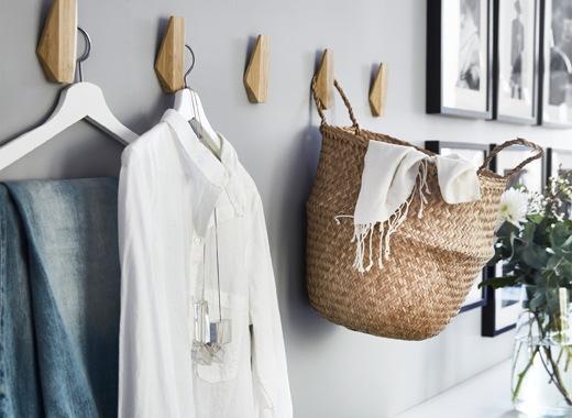 衣物和貯物籃掛在灰色牆上的木掛鈎上。