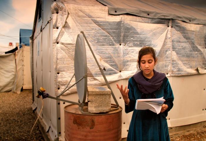 一名女孩在臨時天線和臨時建築物前朗讀書本內容。