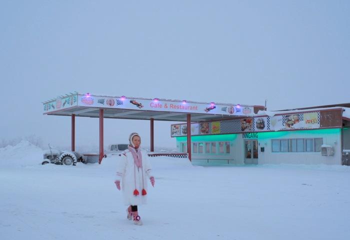 一名女人走在一片荒蕪的雪地上,身後有一間餐廳。