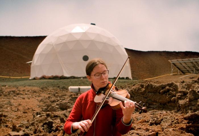 在一片貧瘠之地上,一位女士在一座白色人造建築物前拉小提琴。