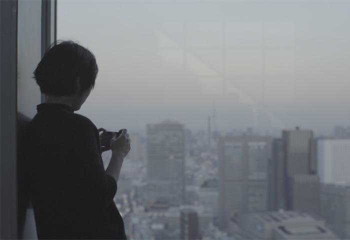一位女人拍攝窗外的城市風景。