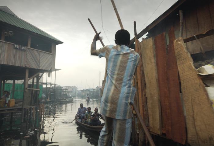 一位穿著彩色西裝的男人撐著小船,穿過水上木棚區。