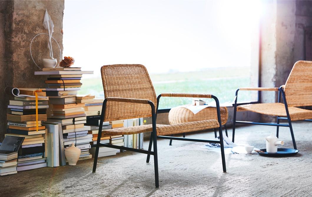 藤和金屬椅子、腳凳,前面放有一堆書及一扇大窗戶。