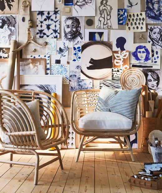 牆上掛滿藝術品,牆前放有兩張織藤扶手椅。
