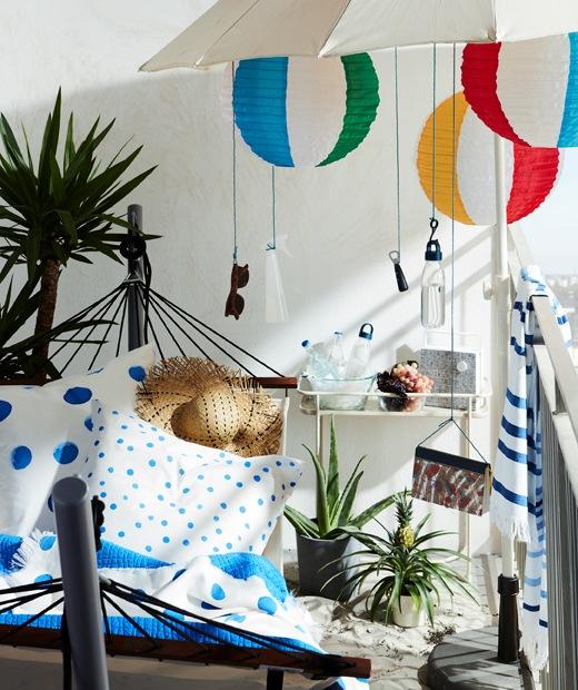 採用海灘風格布置的露台一角,備有吊床連架及太陽傘,太陽傘掛著太陽眼鏡及LED燈等物品。
