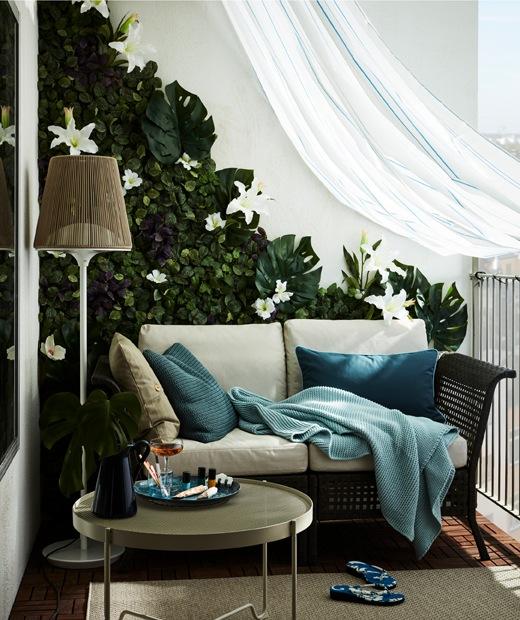 擺放兩座位梳化的露台,牆上飾以人造花,並掛有一幅防水浴簾。