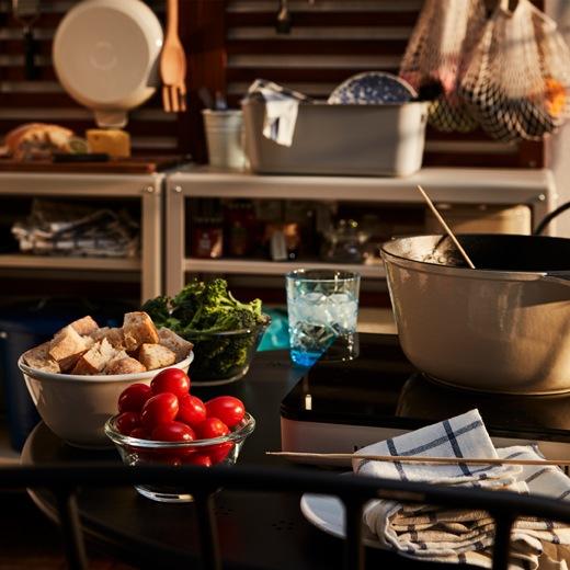 放在露台小圓檯上的二人火鍋用品,背後可看到部分戶外廚房。