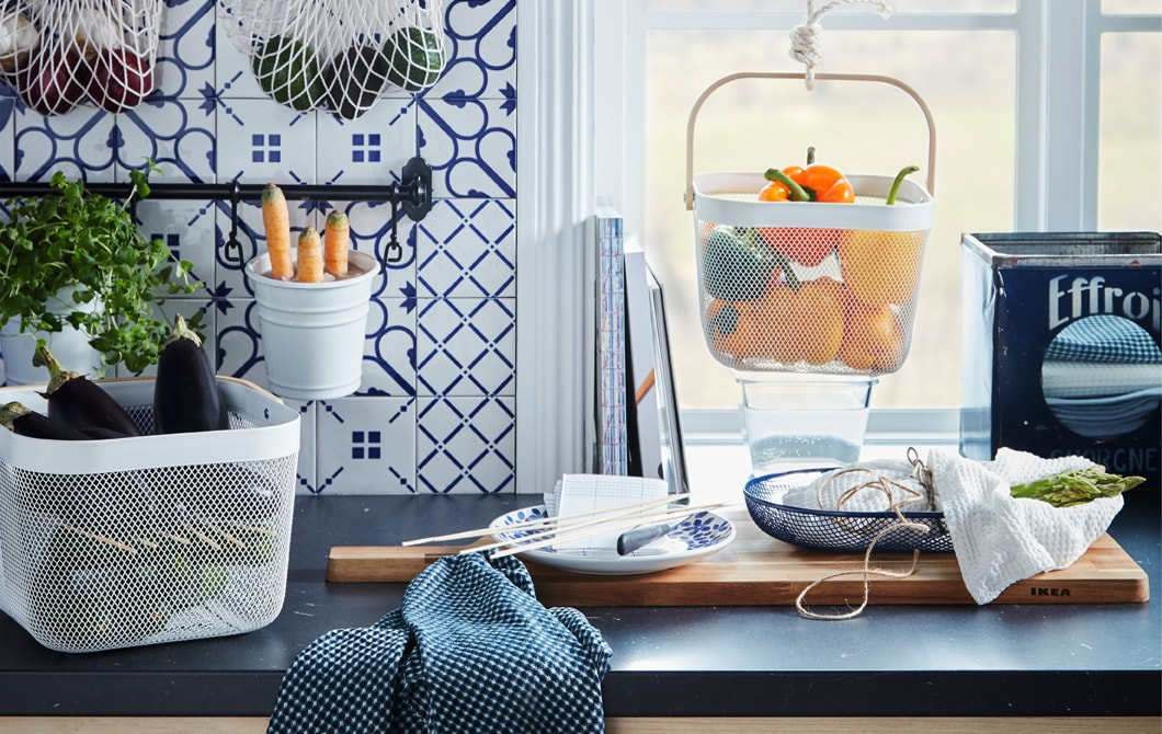 Kitchen worktop with various produce kept in hanging and standing containers, like KUNGSFORS nets and RISATORP baskets.