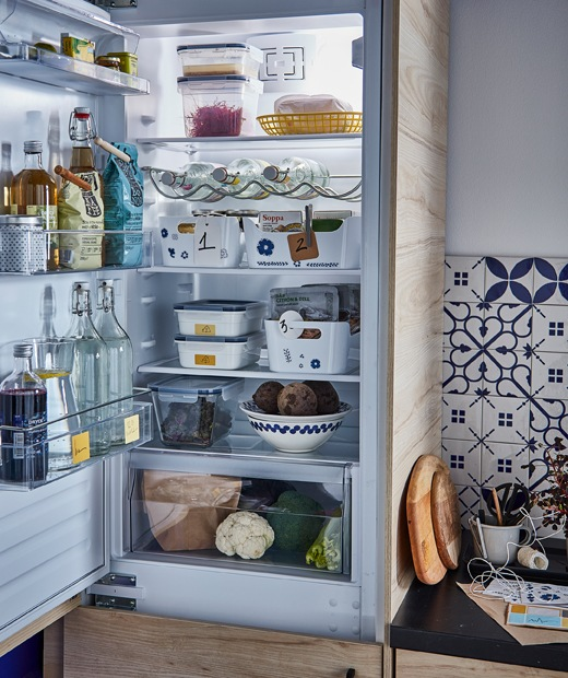 An open fridge with food and drink: bottles in the door, containers on the shelves, drawer for vegetables at bottom.