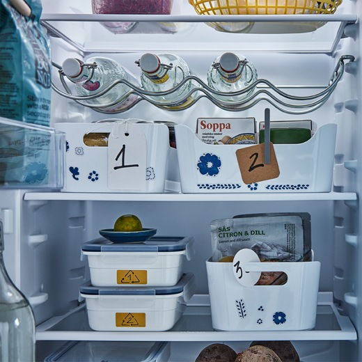 Refrigerator interior with various containers and boxes, some of which have numbered tags attached, on the shelves.