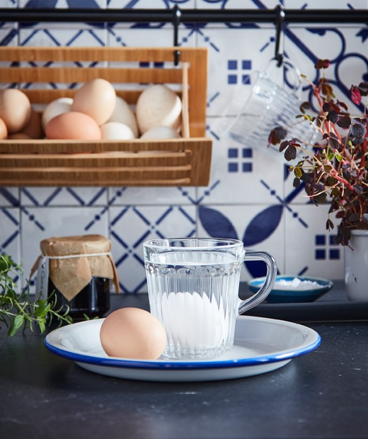 Eggs on a plate, where one egg lies at the bottom of a water-filled DRÖMBILD glass mug. Egg basket hanging in back.