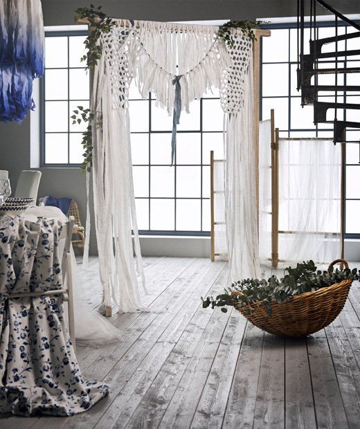 A wedding curtain backdrop made from white cotton fabric strips that were tied to a TÄNKVÄRD rattan room divider.