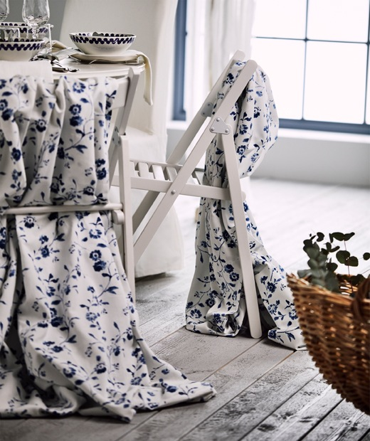 Two white folding chairs draped with white and blue flower patterned BLÅGRAN fabric, standing next to a festive table.
