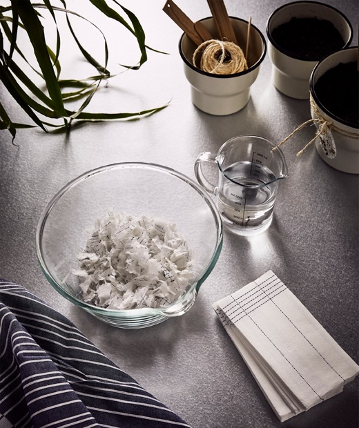 VERKLIGHET paper napkins, a big glass bowl with some shredded paper napkins and a jug of water beside it.
