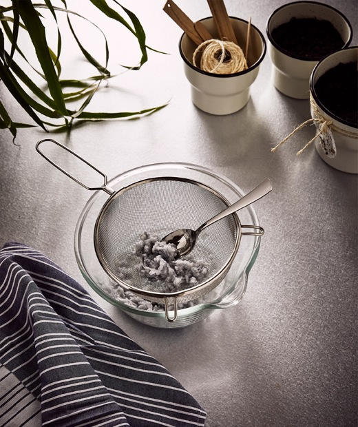 A big glass bowl with an IDEALISK strainer containing moist paper pulp from shredded napkins, beside three plant pots.