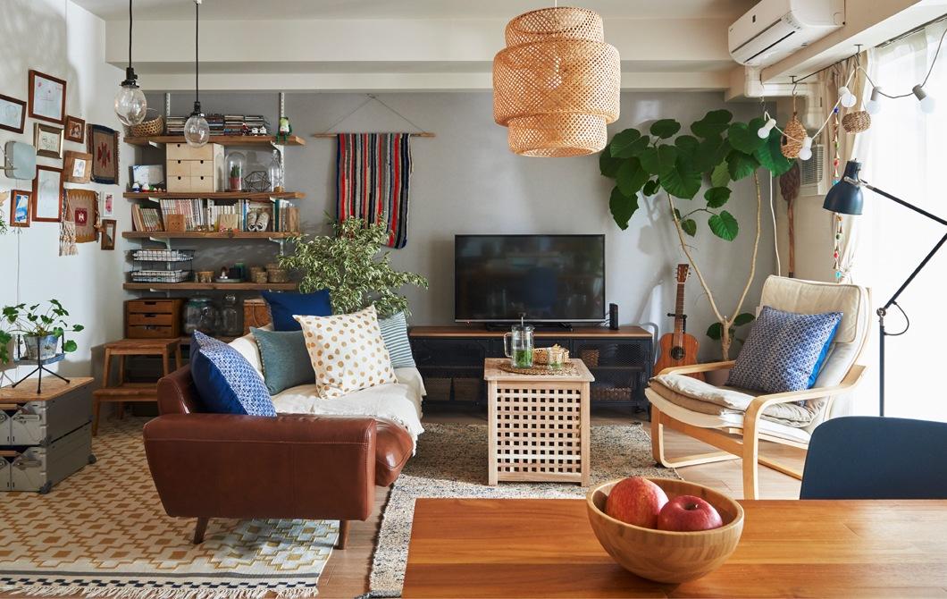 客廳裡有梳化、扶手椅、檯、層架和電視組合,角落還有一盆大植物。