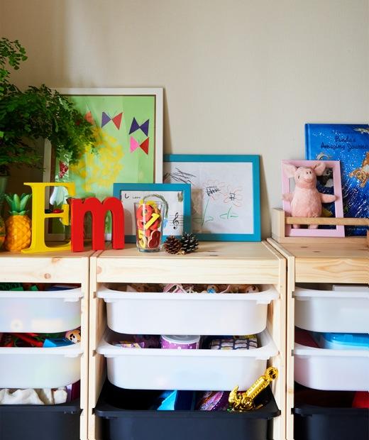 玩具放在木框層架的膠盤裡,層架上方有植物、畫作和書籍。