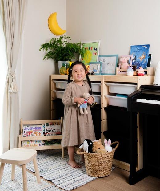 Mieko女兒站在客廳玩具貯物組合旁的照片。