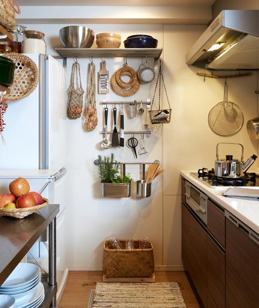 狹窄的廚房擺放黑色廚櫃,廚具則掛在牆上的金屬掛桿和層架。
