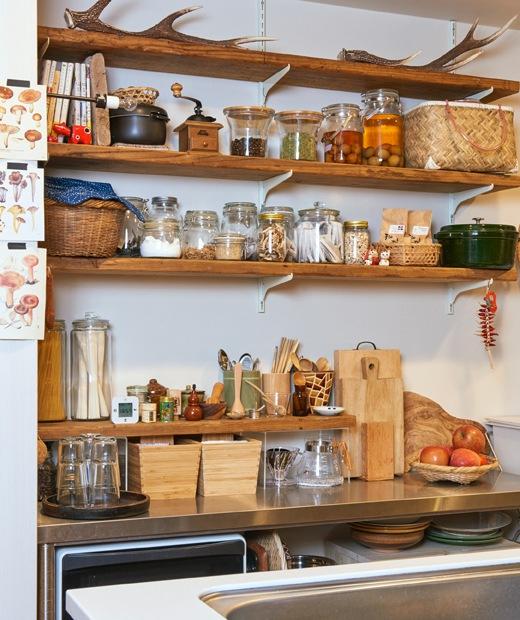 金屬櫃台板上方的木製層架放有一罐罐食材和醃菜,檯面放有木製貯物盒和木板。