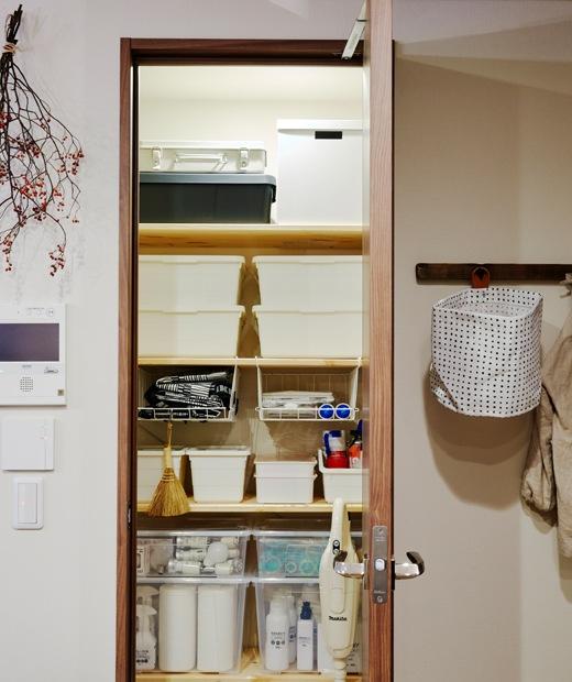 一個打開的廚櫃內疊放了多個白色貯物盒。